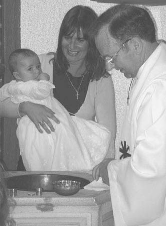 A baptism: baby, mother and Fr Michael